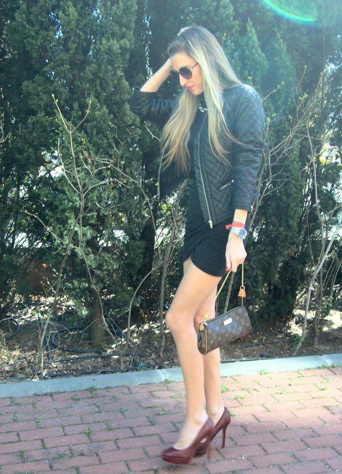 Falda drapeada combinada con chaqueta de cuero, zapatos de plataforma y bolso de Louis Vuitton